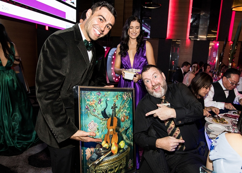 Guest Putting in a Bid for a framed artwork at the Aussie Kidz Charity Gala in Brisbane